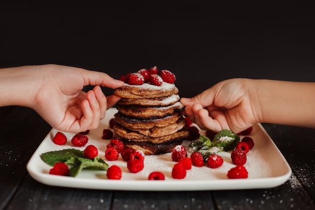 I bambini mangiano frittelle al cioccolato con lamponi freschi e menta su sfondo nero