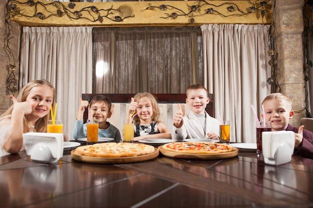 I bambini mangiano la pizza in un ristorante.