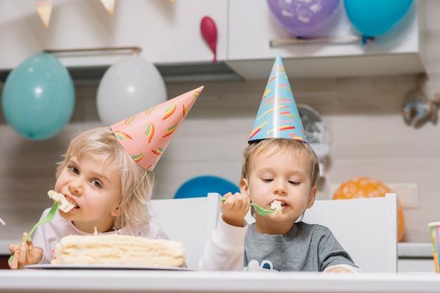 I bambini mangiano la torta sulla festa di compleanno