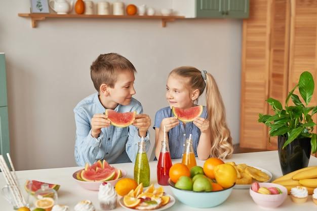 I bambini mangiano le fette di anguria in cucina