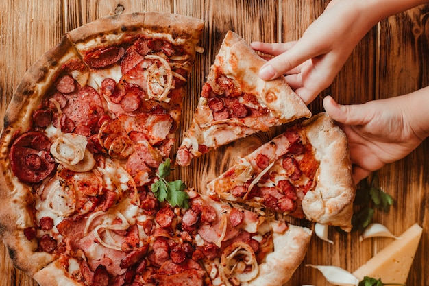 I bambini mangiano pizza con salame e mozzarella