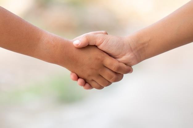 I bambini mostrano il segno di cooperazione tenendosi per mano o stringono la mano