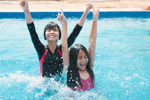 I bambini nuotano e giocano in piscina con un sorriso felice