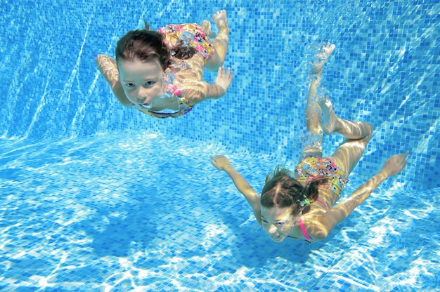 I bambini nuotano in piscina sott'acqua, le felici ragazze attive si divertono in acqua, i bambini fitness e lo sport in vacanza attiva in famiglia