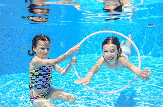 I bambini nuotano in piscina sott'acqua, le felici ragazze attive si divertono sott'acqua, i bambini fanno sport in vacanza con la famiglia