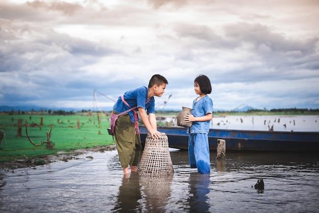 I bambini pescano e si divertono nel canale. stile di vita dei bambini in campagna della tailandia.
