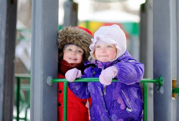 I bambini piccoli in abiti invernali divertirsi sul parco giochi al giorno di inverno nevoso. i bambini giocano all'aperto. all'aperto attivo per le vacanze in famiglia
