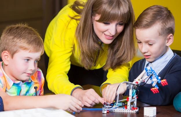 I bambini positivi giocano e assemblano il costruttore nella stanza dei bambini.