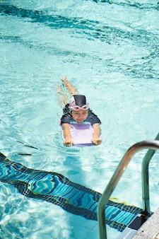 I bambini praticano il nuoto in piscina.