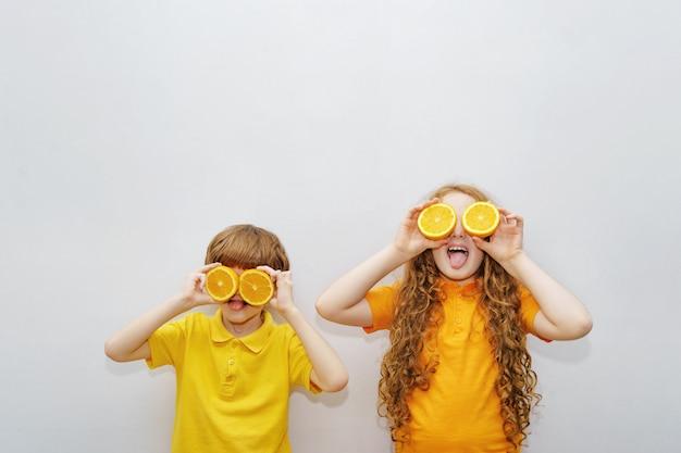 I bambini ridenti con gli occhi arancioni mostrano denti bianchi e sani.