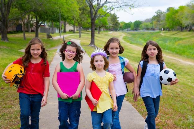 I bambini scherzano le ragazze che vanno a scuola con palloni sportivi
