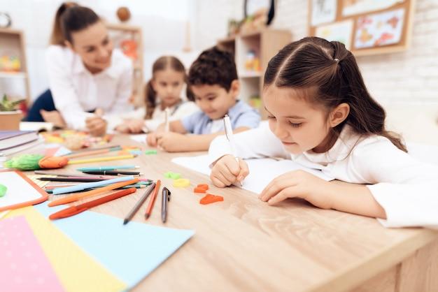 I bambini scrivono nei quaderni con una penna.