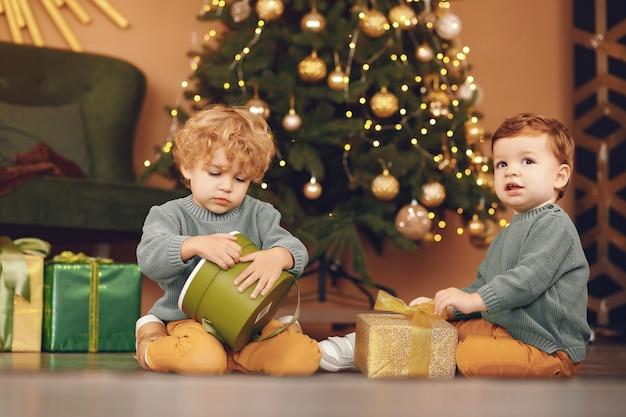 I bambini si avvicinano all'albero di natale in un maglione grigio