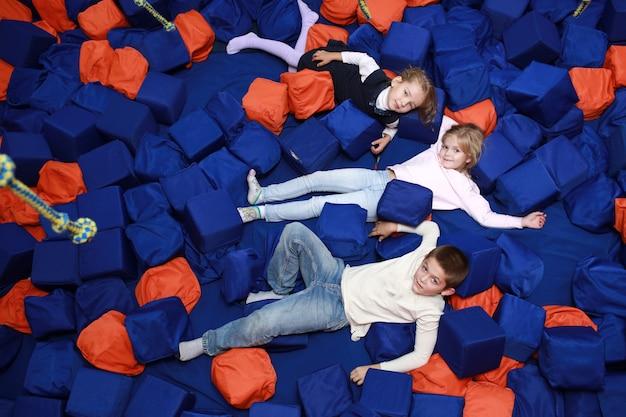 I bambini si divertono in piscina con morbidi cubetti. centro di intrattenimento per bambini. infanzia felice
