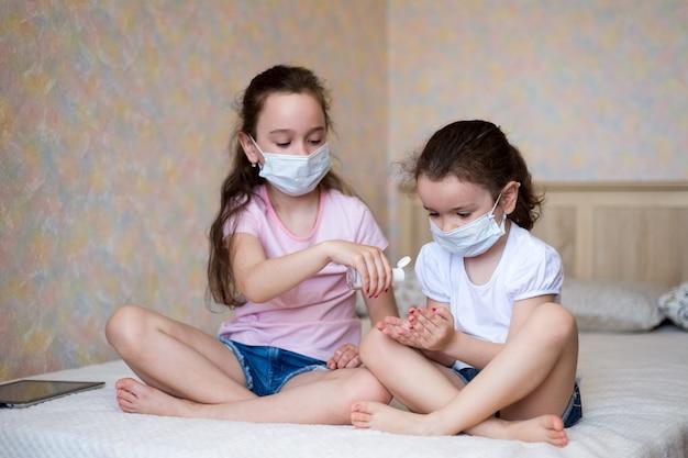 I bambini si lavano le mani con gel alcolico per prevenire la diffusione di infezioni del virus corona ed evitare i batteri