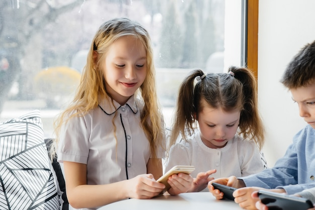 I bambini si siedono a un tavolo in un bar e giocano a telefoni cellulari insieme. intrattenimento moderno.