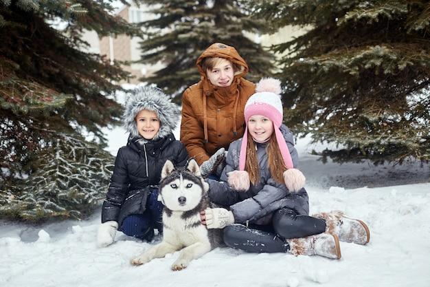 I bambini si siedono sulla neve e accarezzarono il cane husky. i bambini escono e giocano con il cane husky in inverno. camminare nel parco