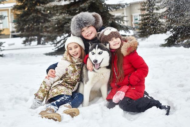I bambini si siedono sulla neve e accarezzarono il cane husky. i bambini escono e giocano con il cane husky in inverno