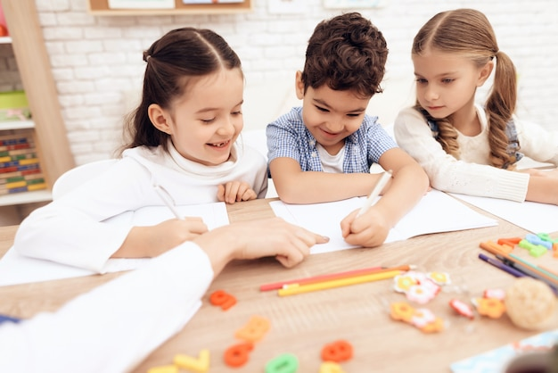 I bambini sorridono e scrivono in quaderni con una penna.