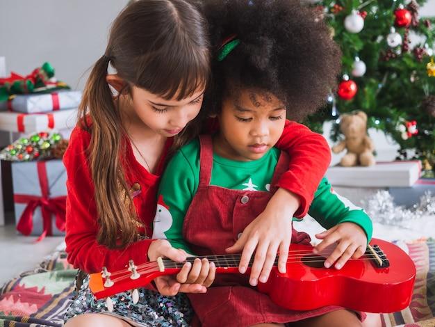 I bambini suonano felicemente la chitarra il giorno di natale con l'albero di natale