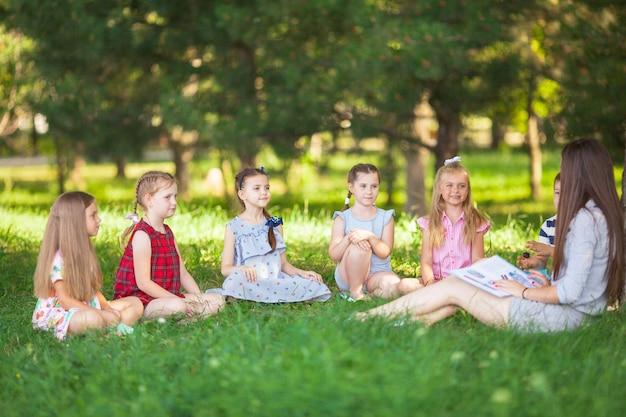 I bambini tengono una lezione con l'insegnante nel parco su un prato verde.