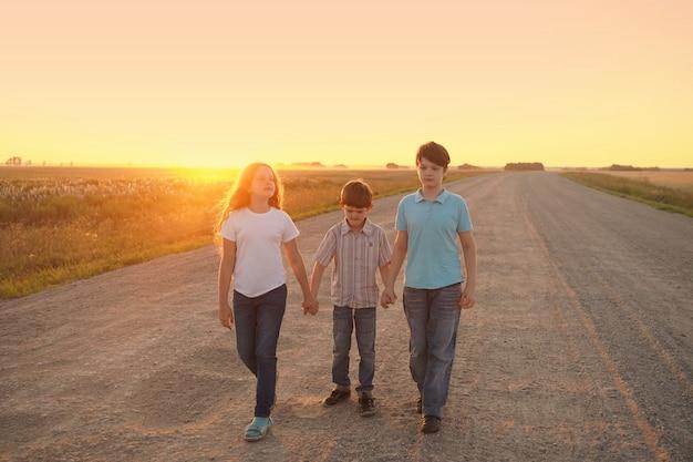 I bambini vanno sulla strada per incontrare il tramonto.