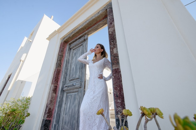 I bei capelli biondi giovani donne sposa blu in un abito bianco lungo sexy di nozze a santorini in grecia