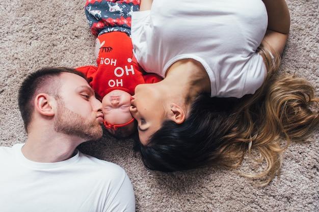 I bei genitori baciano la loro figlia e mentono sul pavimento