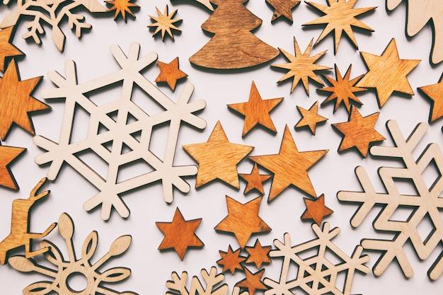 I bei precedenti di natale con molte piccole decorazioni di legno sullo scrittorio bianco.