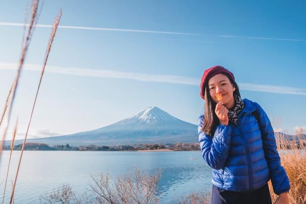 I bei turisti sorridenti asiatici della donna stanno viaggiando e si sentono felici nel campo di erba asciutta