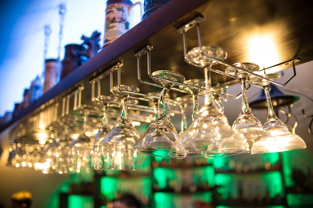 I bellissimi bicchieri da cocktail al bar sono appesi