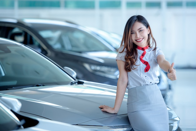 I bellissimi venditori asiatici sono felici di vendere nuove auto nello showroom e far venire i clienti a comprare auto presso i concessionari.