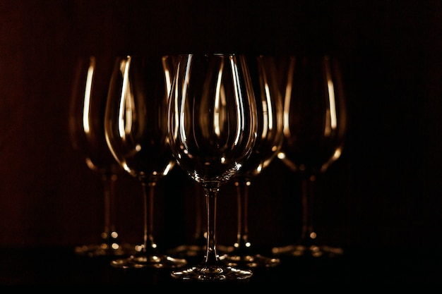I bicchieri da vino illuminati con luce calda stanno su sfondo nero