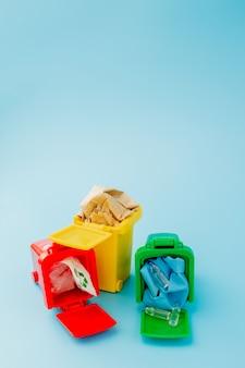 I bidoni di riciclaggio gialli, verdi e rossi con riciclano il simbolo sull'azzurro. mantieni la città in ordine, lascia il simbolo del riciclaggio