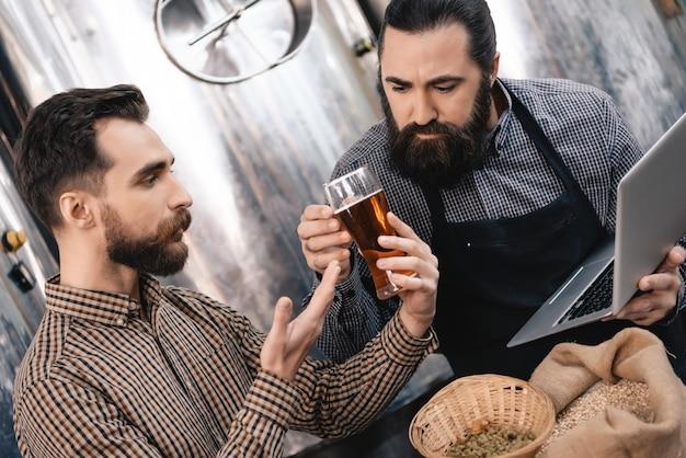 I birrai dubitano della qualità della birra. gli uomini tengono il bicchiere.