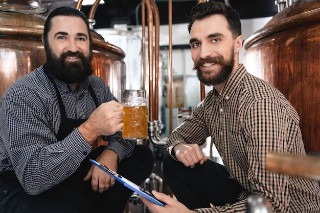 I birrai felici bevono la birra nella fabbrica della pianta di birra.