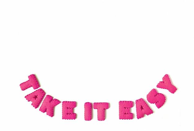 I biscotti a forma di alfabeto rosa che compitano la parola lo rendono facile su fondo bianco