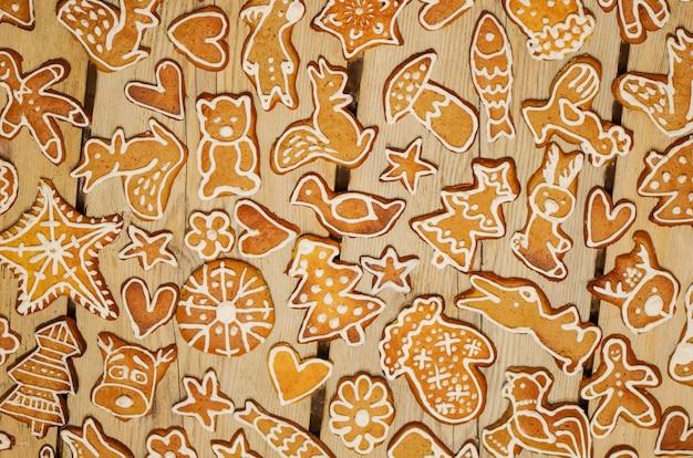I biscotti del pan di zenzero di natale hanno decorato la glassa. biscotti di panpepato di natale sul piano tavolo in legno vista.