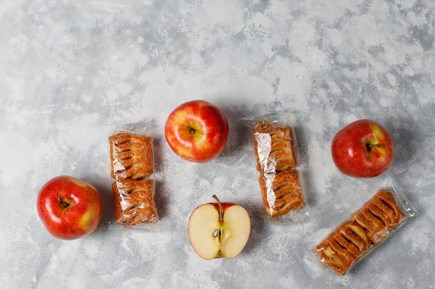 I biscotti della pasta sfoglia hanno riempito di marmellata di mele e mele rosse fresche su calcestruzzo leggero