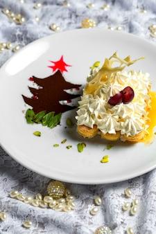 I biscotti di dito decorati con crema sono servito in salsa vicino al piccolo albero di polvere del caffè