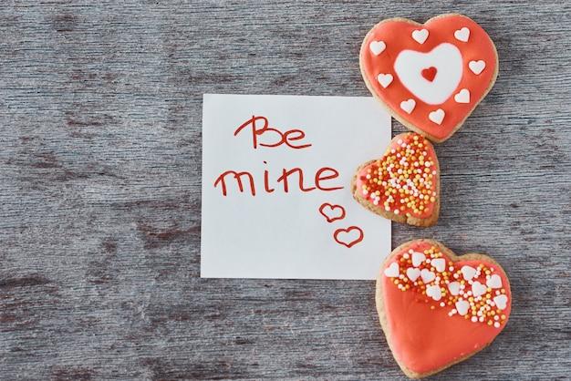 I biscotti e lo strato di carta di forma del cuore di deocrated con l'iscrizione sono i miei su gray. concetto di san valentino