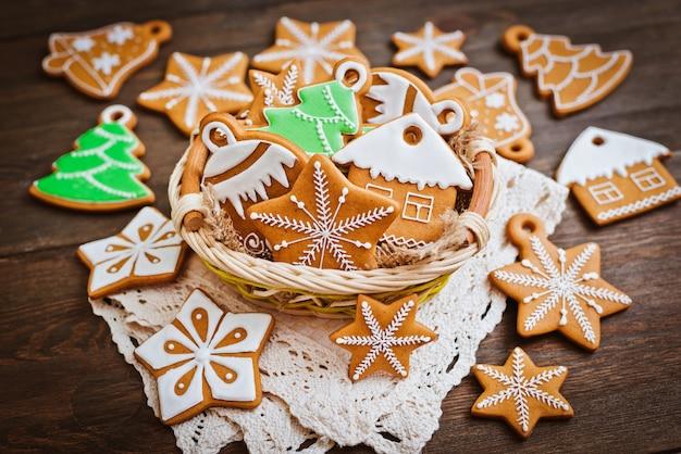 I biscotti festivi del pan di zenzero di natale a forma di stella si trovano su un marrone scuro di legno.