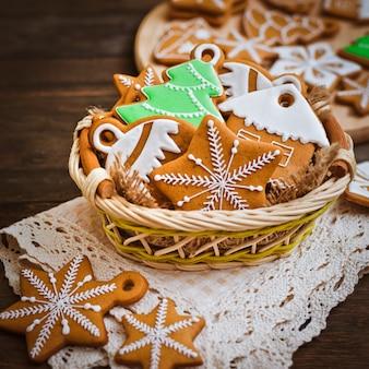 I biscotti festivi del pan di zenzero di natale a forma di stella si trovano su una tavola di legno di marrone scuro