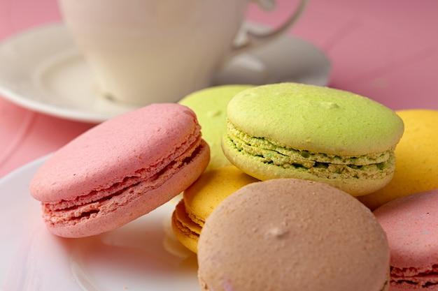 I biscotti francesi del maccherone dei colori luminosi sono servito in piatto ceramico bianco