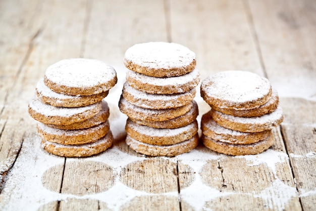 I biscotti freschi dell'avena impila con la polvere dello zucchero sulla tavola di legno rustica