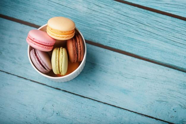 I biscotti maccheroni sono collocati in un piatto bianco su uno sfondo di legno blu.
