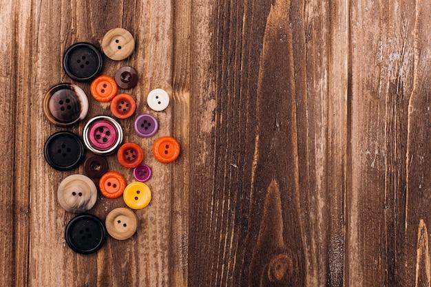 I bottoni variopinti per l'artigianato si trovano sulla tavola di legno