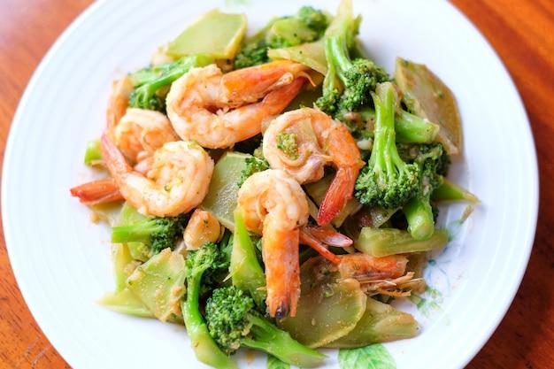 I broccoli fritti scalpore calde con gambero gigante servono sul piatto - concetto dell'alimento.