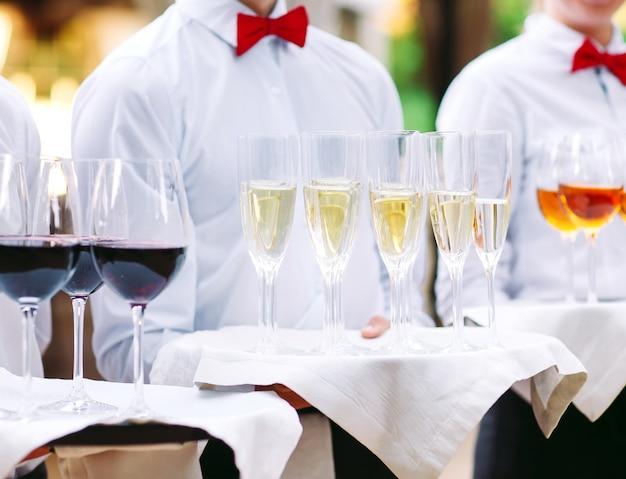 I camerieri accolgono gli ospiti con bevande alcoliche. champagne, vino rosso, vino bianco su vassoi.