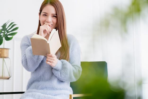 I capelli lunghi della bella donna asiatica godono del momento di fine settimana con il fondo della stanza bianca del libro della tenuta della mano